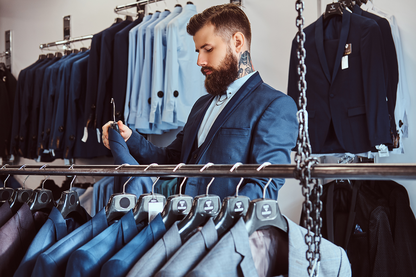 Elegantly dressed bearded male with tattoos on hands and neck chooses new costume in menswear store.