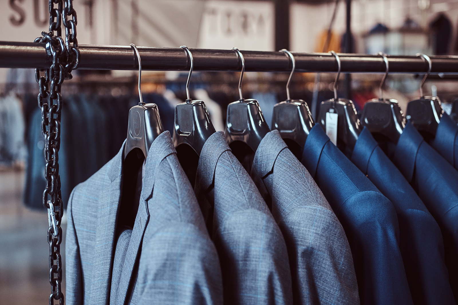 Photo of a rack with suit jackets in menswear store.